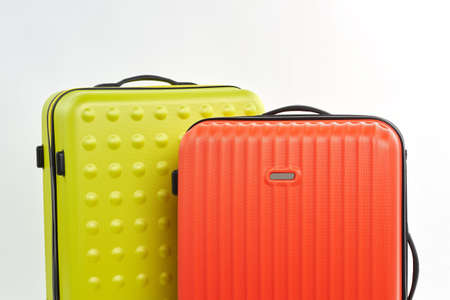Suitcases for travelling, white background. Cropped image of colorful wheeled bags.
