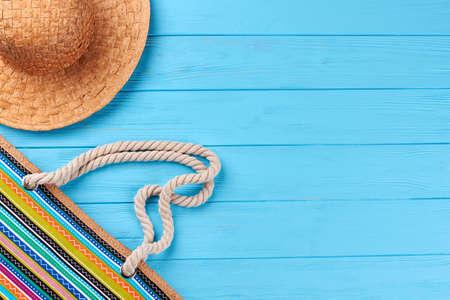 Part of hat and handbag, blue background. Handmade straw headgear, textile bag, vintage background.
