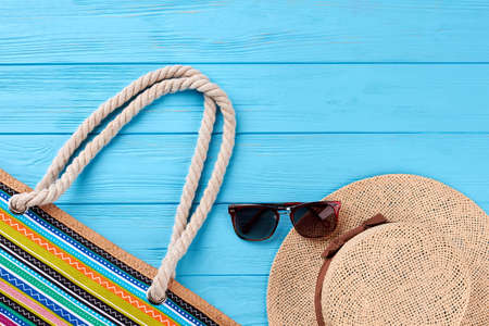 elementos de protección personal: Straw hat, sunglasses, female handbag. Beach items on wooden background. Foto de archivo