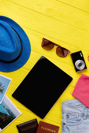 foto carnet: Black modern tablet, photo camera. Traveler modern accessories, yellow background. Summer fashion style set. Foto de archivo
