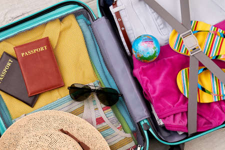 velure: Suitcase with different traveler items. Packed luggage for family summer trip.