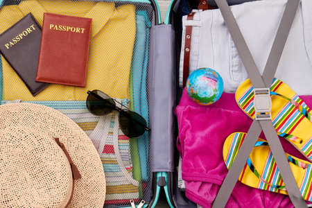 velure: Close up of packed suitcase. Essential stuff for summer resort in traveler bag.