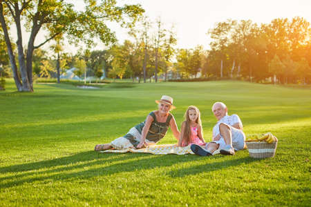 Child with grandparents having picnic. Happy people relaxing. Importance of relationships with grandkids.