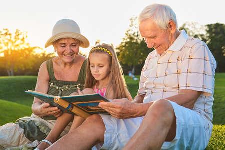 Enfant avec les grands-parents, album photo. Des gens heureux en regardant des photos. Banque d'images - 84792411