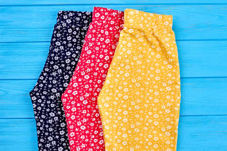 Organic baby girl pants close up. Collection of three pairs natural trousers for little girl, top view.