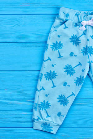 Cropped image of modern baby leggings. Close up of printed fashion spring pants for children. Trendy clothes for kids.
