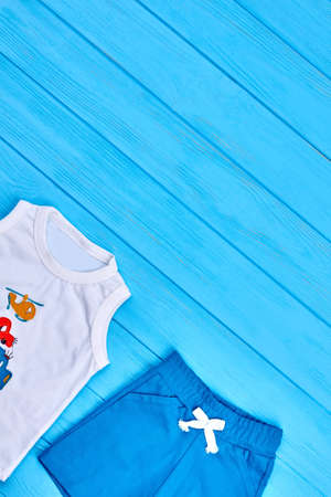 Baby boy summer casual clothes. White t-shirt and blue shorts for little boy on wooden background, copy space.