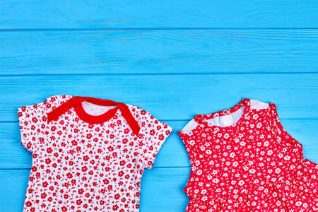 Cute baby girl summer wear. Infant girl printed bodysuit and dress on blue wooden background, copy space. Casual clothing for infant baby girl.