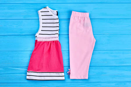 Toddler girl summer cotton clothes. New collection of summer clothing for little girls on blue wooden background. Kids fashion style. Stock Photo
