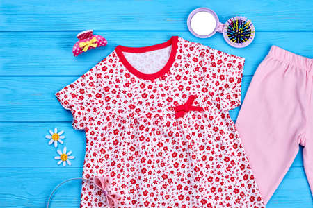 Little girl garment and accessories. Infant baby flower print cotton dress and pink leggings, hair accessories on blue wooden background. Stock Photo