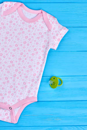 Bodysuit with pattern of small flowers. Baby-girl soft organic summer romper and toy on blue wooden background. Stock Photo