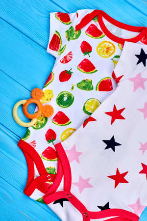 Beautiful modern cotton baby bodysuits. Collection of adorable organic rompers for infant childs, toy, top view. Toddler baby cotton apparel. Stock Photo