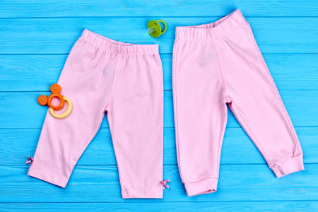 Collection of trendy stretch baby leggings. Modern colored pants for baby-girl, pacifier. Cotton pink baby-girl summer capri, accessories. Natural kids clothes.