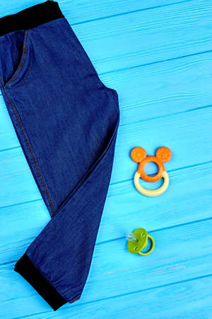 Kids jeans and accessories, top view. New denim trousers for infant baby, toy, pacifier, blue wooden background.