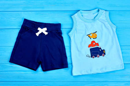 small business: Baby-boy trendy cotton summer suit. Dark blue textile shorts and cartoon transport t-shirt for little boys. Newborn boy summer outfit. Stock Photo