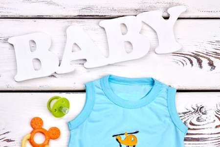small business: Baby boy cute t-shirt, accessories. Infant boy sleeveless cotton t-shirt, pacifier, teether, text baby, old wooden background.