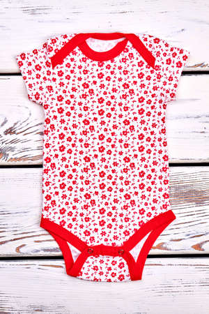 romper: Baby girl white and red bodysuit. Newborn baby-girl soft bodysuit with a pattern of small red flowers, white wooden background.