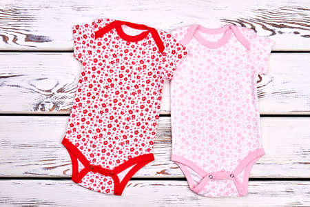 Baby-girl collection of soft bodysuits. Baby-girl beautiful design rompers on white wooden background, top view. Red and pink floral print bodysuits for kids. Stock Photo