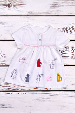 Baby-girl cute summer dress. New white cartoon summer dress for infant girl, old wooden background, top view. Stock Photo