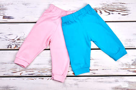 Collection of new kids trousers. Infant girls and boys colored pants on white wooden background. Childs organic apparel on sale. Stock Photo