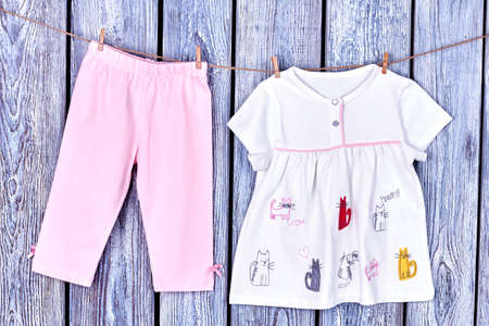 Baby clothes hanging on clothesline. Clothesline with hanging baby apparel on grey wooden background.