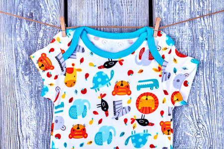 romper: Infant baby t-shirt hanging on rope. Newborn kids apparel drying on clothesline on grey wooden background.