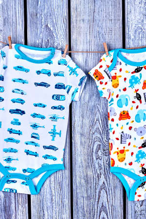romper: Baby boy rompers hanging on clothesline. Infants summer wear drying on rope on old wooden background.