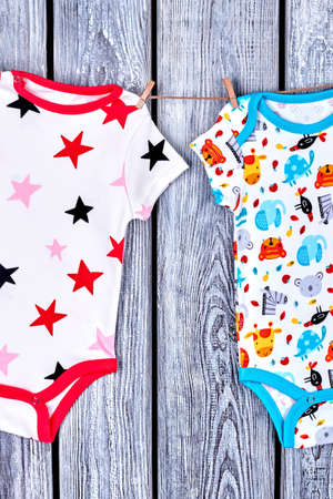 romper: Babies rompers drying on rope. Clothesline with hanging kids bodysuits on old wooden background. Childs garment in laundry. Stock Photo