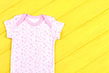 romper: Infant girl soft cotton t-shirt. Baby-girl beautiful brand bodysuit on yellow wooden background. Infants summer clothing on sale.