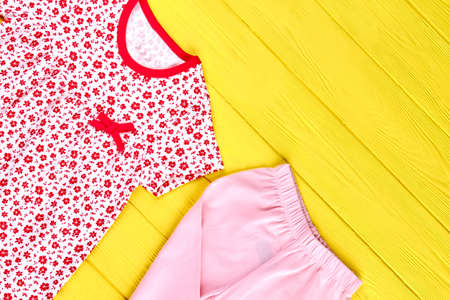 Baby-girl high quality clothes. Toddler girl adorable patterned dress and pink leggings, yellow wooden background. Kids new apparel on sale. Stock Photo