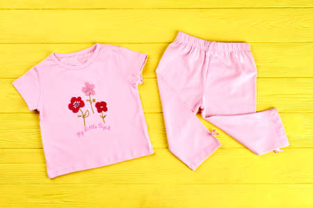 Baby-girl beautiful cotton suit. Infant girl pink t-shirt and leggings on yellow wooden background. Babies brand apparel on sale. Stock Photo