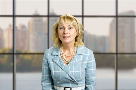 Portrait of smiling mature woman. Middle aged woman smile while standing on office window background.