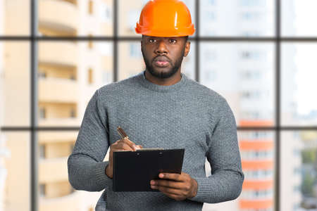 Portrait of architect with clipboard. Young engineer write on clipboard and looking straight on blurred background.