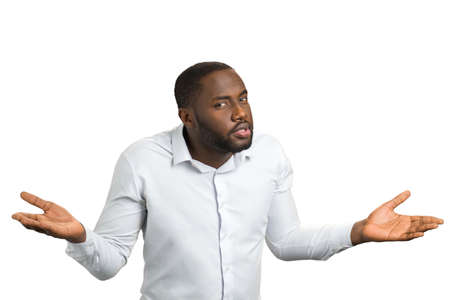 Black man with hands in different sides. Confused man in white shirt spreads his hands to the sides in surprise. Mistake or suspicion concept.
