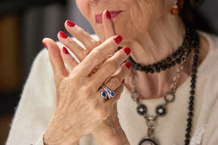 Old womans manicured hands with ring. Old luxury woman beautiful hands with red nails and silver ring. Aged woman keeping hands with red manicure together.