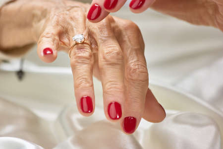 Female finger indicating on diamond. Senior woman with red nails showing her golden ring with precious jewels. 版權商用圖片