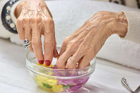 Spa treatment for female hands. Old woman hands having manicure and spa. Caucasian woman hands in bowl with water. Nail care concept.