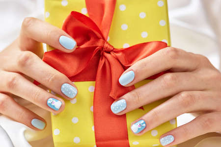 Beautiful gift box in female hands. Woman hands with winter manicure holding yellow gift box with red ribbon close up. Stock Photo