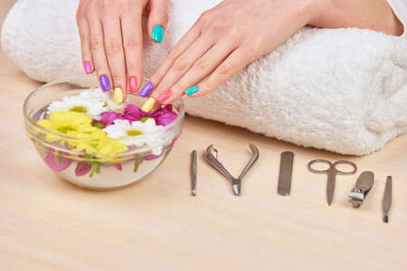 Female hands in bowl with water. Woman gentle hands on glass bowl with aroma water and colorful chrysanthemums. Young woman hands on towel, manicure equipment. Stock Photo