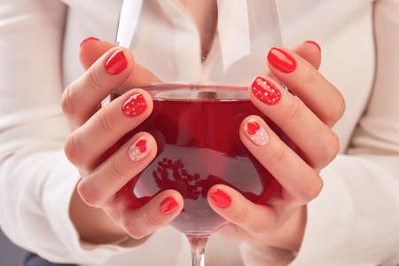 Woman hands holding large glass of wine. Young woman hands with beautiful red manicure holding glass with red wine. Valentines day nail art design. Stock Photo