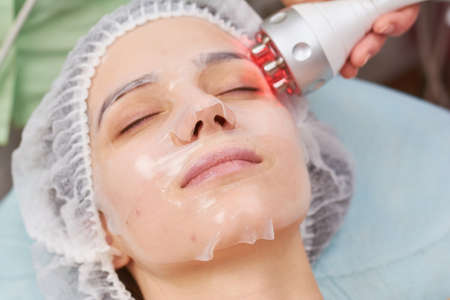 Facial hydrogel mask close up. Woman undergoing skin treatment.