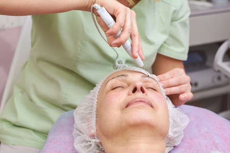 aging woman: Ultrasonic face cleaning procedure. Work of cosmetician, mature woman. Slowing down skin aging.