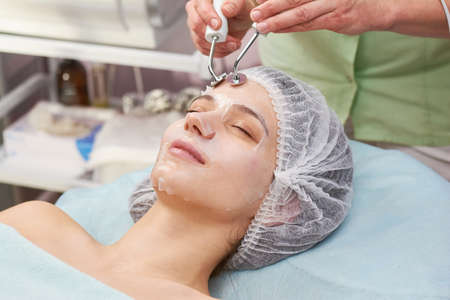 Microcurrent therapy, young woman. Caucasian girl at the cosmetologist. Electricity as a cure.