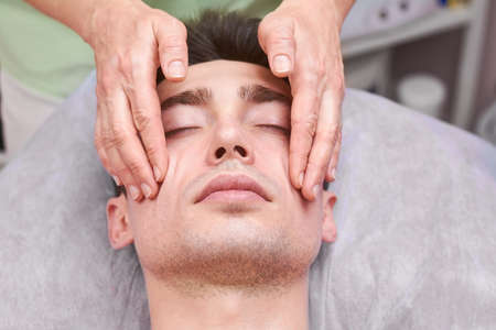 Handsome guy, face massage. Hands of a masseuse working.