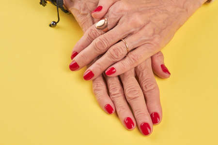 salon background: Female hands with beautiful red manicure. Senior woman hands with red nails polish on yellow salon table. Nail salon and spa.