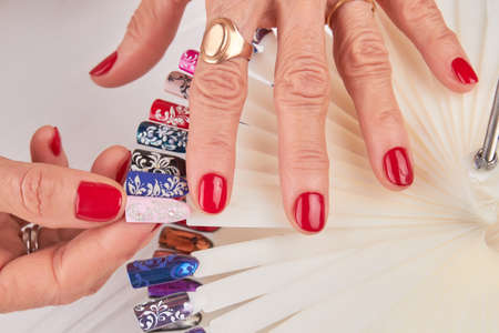 Female hands with beautiful red manicure. Close up of old woman manicured hands holding nail color art samples. Woman in nail salon.