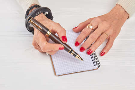 Female hands with luxury pen and notebook. Old woman manicured hands with pen and empty notebook, white wooden background. Stock Photo