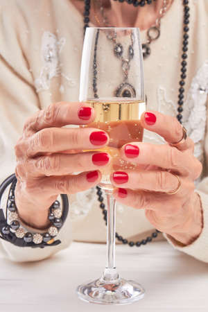 Female hands holding glass of champagne. Well-groomed woman hands holding glass of champagne close up.