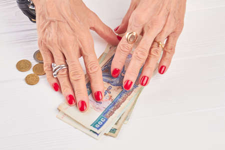Red manicure and Burma banknotes. Senior woman well-groomed hands and kyat money, white wooden background.