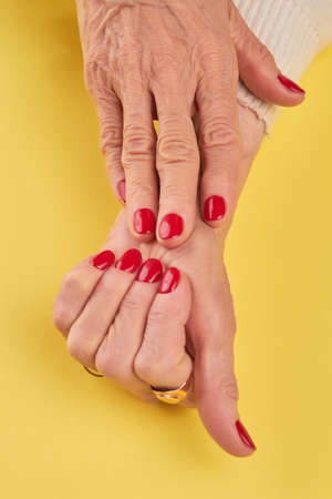 salon background: Old woman hands with red manicure. Female manicured hands on yellow background close up. Skin and nails spa and care. Stock Photo